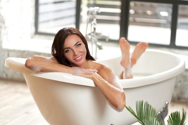 Retrato mujer hermosa relajante tumbado en la bañera en el baño.