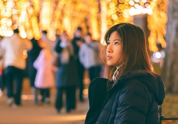 Retrato de mujer hermosa en ropa de invierno con luz de navidad