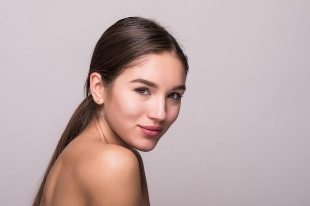 Retrato de mujer hermosa con rostro perfecto en pared blanca
