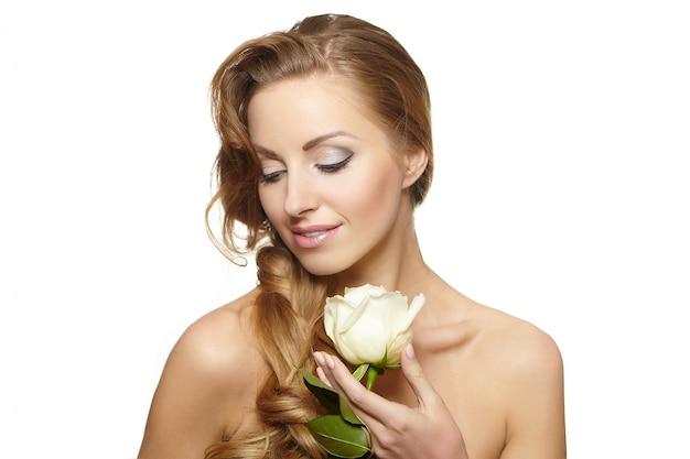 Retrato de mujer hermosa sensual sonriente con rosa blanca sobre blanco