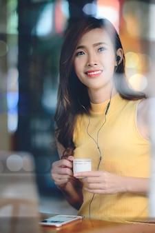 Retrato de mujer hermosa sentada en el café con luz de noche
