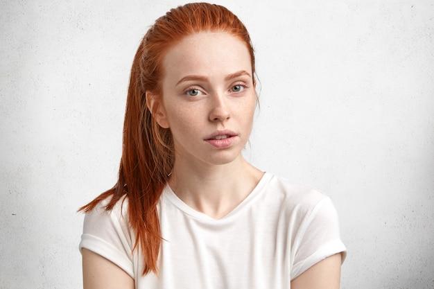 Retrato de mujer hermosa seria de jengibre con piel pecosa, vestida con camiseta blanca casual, tiene expresión pensativa, posa contra la pared de hormigón.