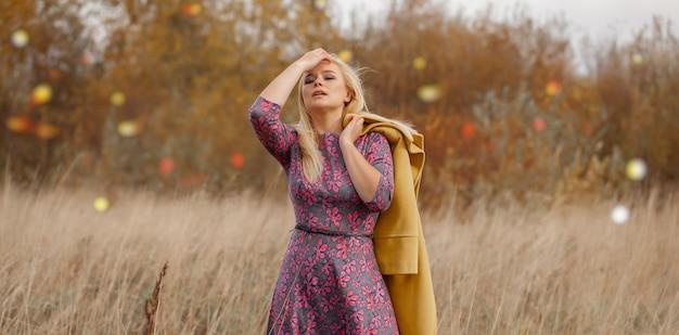 Retrato de mujer hermosa sexy en vestido rosa, abrigo amarillo, maquillaje ahumado, pelos voladores en hierba seca