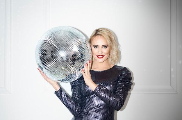 Retrato de mujer hermosa sosteniendo la bola de discoteca en la pared blanca