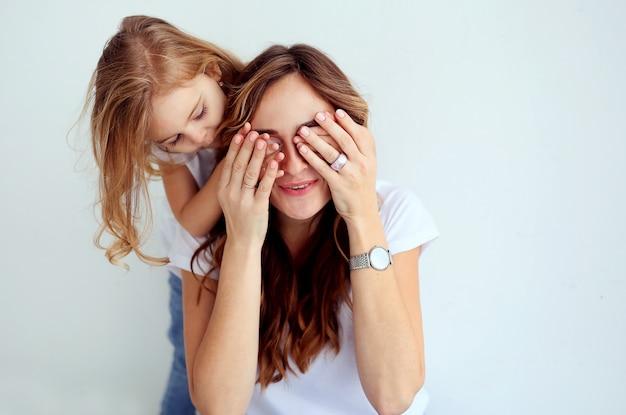 Retrato de mujer hermosa con su linda hija divirtiéndose juntos.