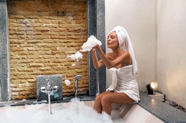 Retrato de mujer hermosa con una toalla sobre su cabeza y soplando espuma mientras toma un baño