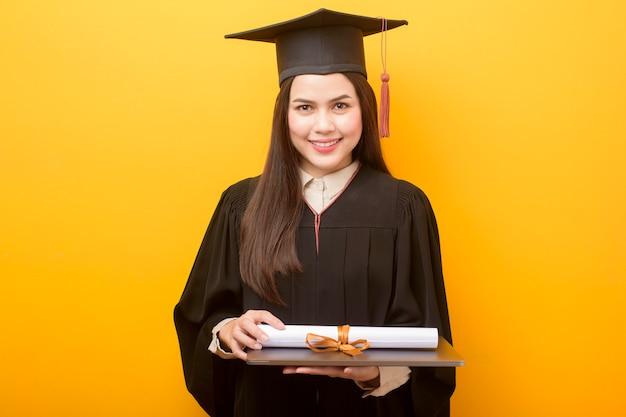 Retrato de mujer hermosa en toga de graduación está sosteniendo la computadora portátil sobre fondo amarillo