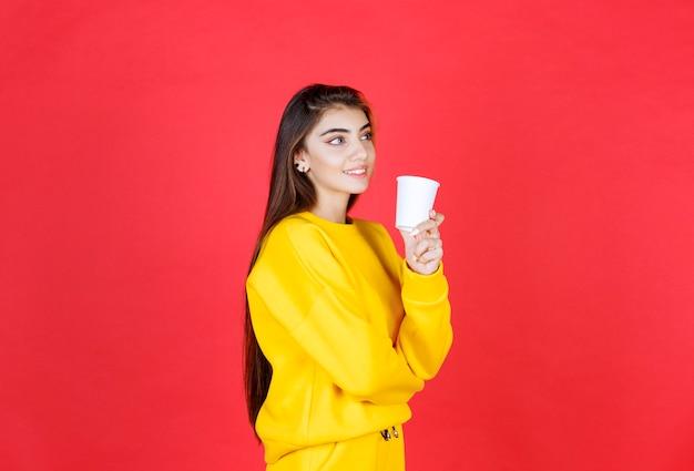 Retrato de mujer hermosa en traje amarillo posando con taza de té