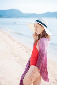 Retrato de mujer hermosa en traje de baño rojo relajante en la playa