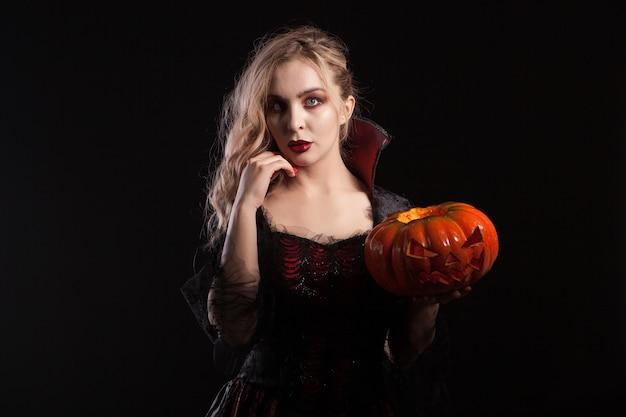 Retrato de mujer hermosa vampiro con calabaza de halloween. mujer vampiro seductora.