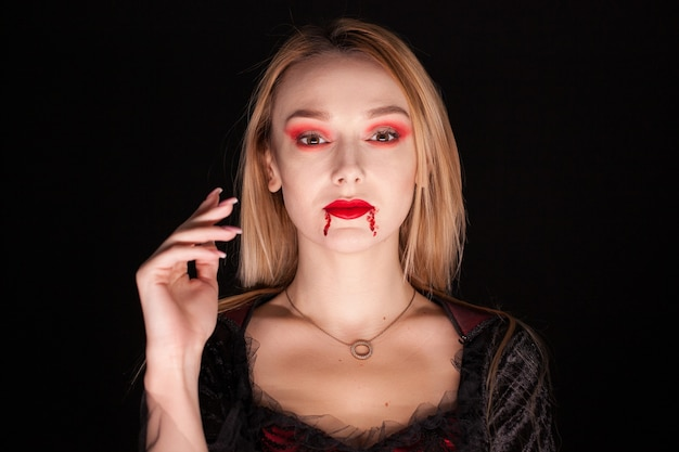 Retrato de mujer hermosa vampiro sobre fondo negro. vampiro atractivo.