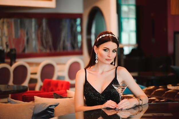 Retrato de mujer hermosa con vaso de martini.