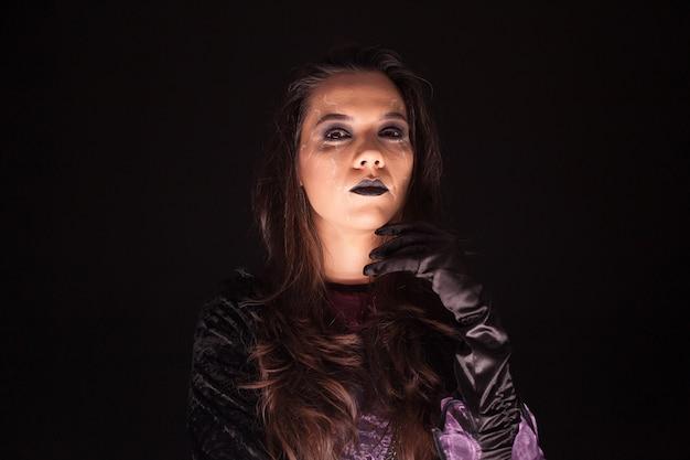 Retrato de mujer hermosa vestida como una bruja sobre fondo negro.