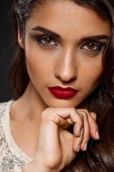 Retrato de mujer hermosa en vestido cremoso con labios rojos