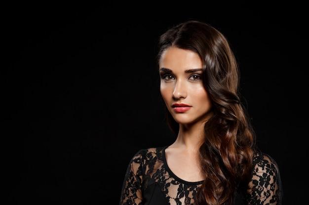 Retrato de mujer hermosa en vestido negro sobre pared oscura