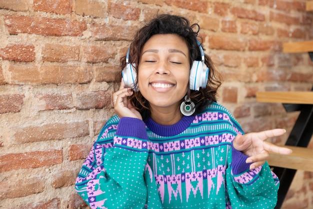 Retrato de una mujer hispana disfrutando de la música. lleva unos auriculares y hace gestos con las manos. espacio para texto.