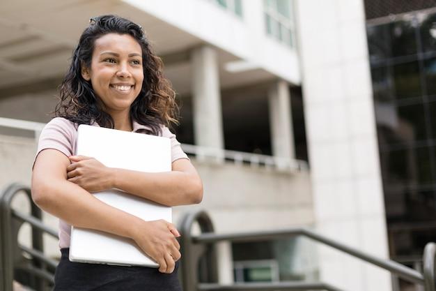 Retrato de mujer hispana joven sonriente sosteniendo la computadora portátil en sus manos al aire libre. espacio para texto.