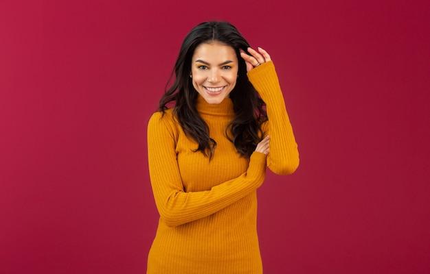Retrato de mujer hispana morena con estilo muy sonriente en suéter amarillo vestido de moda otoño invierno posando aislado en la pared roja