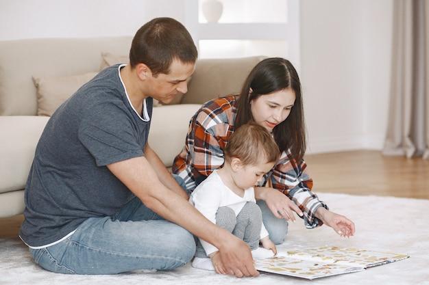 Retrato de mujer y hombre abrazando a su pequeño niño lindo, sentados juntos en el suelo cerca del sofá
