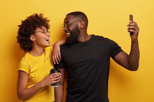 Retrato de mujer y hombre llenos de alegría toman selfie en smartphone moderno