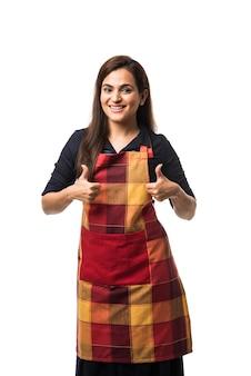 Retrato de mujer india chef o cocinero en delantal que presenta apuntando con el signo de ok pulgares arriba o con las manos dobladas que se encuentran aisladas sobre fondo blanco.