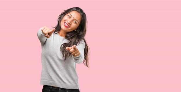 Retrato de mujer india joven alegre y sonriente apuntando al frente