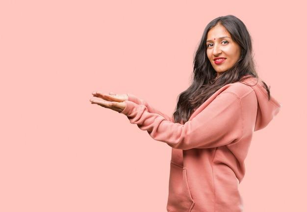 Retrato de la mujer india joven de la aptitud que lleva a cabo algo con las manos, mostrando un producto