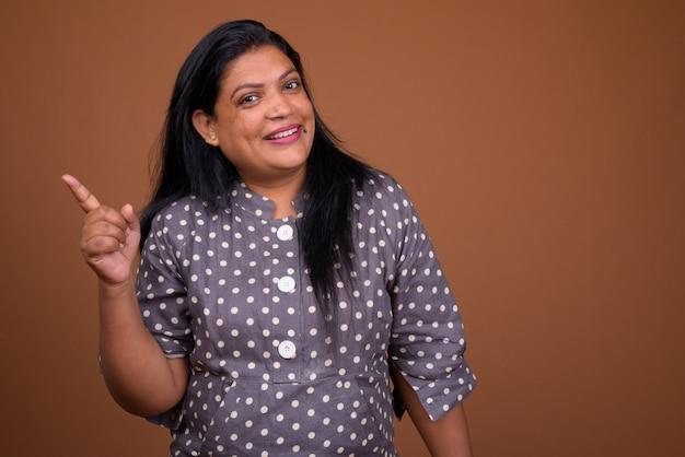 Retrato de mujer india madura contra el fondo marrón