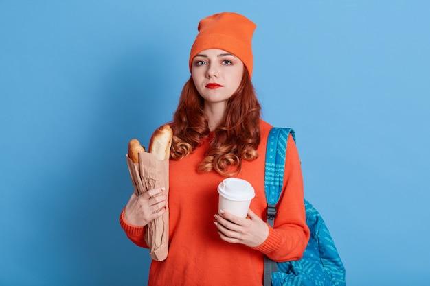 Retrato de mujer infeliz con sombrero y suéter casual, sosteniendo una bolsa de papel con baguettes y café para llevar