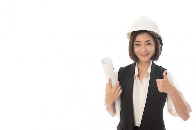 Retrato de mujer ingeniera con un plano en la mano y mostrando los pulgares para arriba aislado en blanco