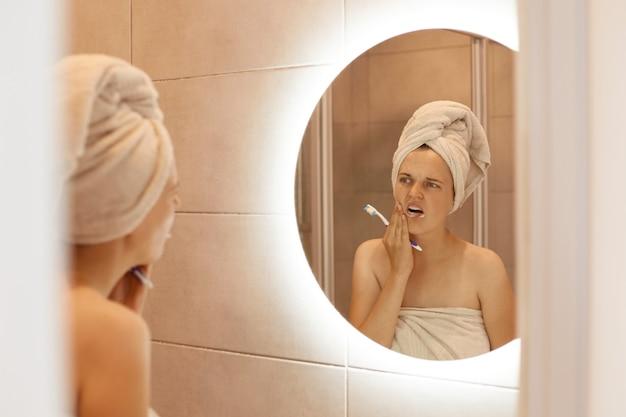 Retrato de mujer insalubre con hombros descubiertos cepillándose los dientes, con procedimientos de higiene después de tomar una ducha, problemas dentales, siente un fuerte dolor.
