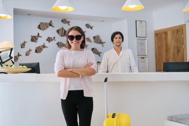 Retrato de mujer invitada con maleta, hombre trabajador de hotel cerca de recepción