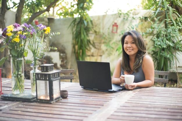 Retrato de mujer japonesa con portátil en el patio trasero. hermosa chica con cabello castaño comprando o charlando en línea, divirtiéndose, viendo películas, trabajando por cuenta propia. bebiendo café