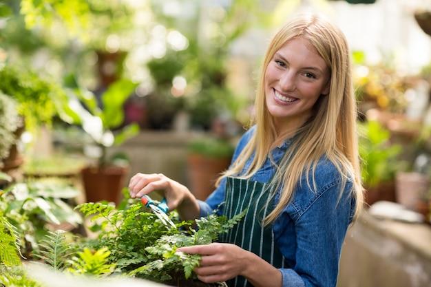 Retrato de mujer jardinero sonriendo mientras poda