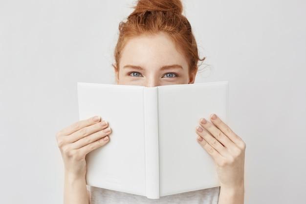 Retrato de mujer de jengibre escondido detrás del libro.
