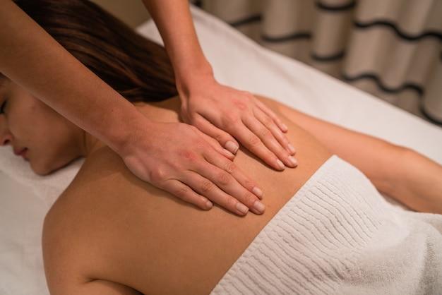 Retrato de mujer joven acostada sobre el tratamiento de mesa y recibiendo un relajante masaje de espalda en el salón de spa.