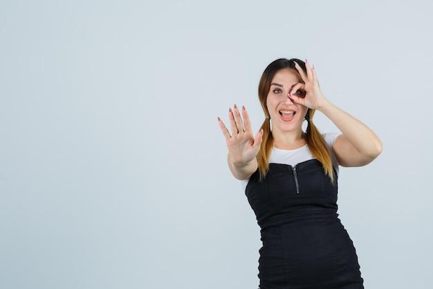 Retrato, de, mujer joven, actuación, ok, señal, en, ojo, y, parada, gesto