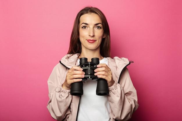 Retrato de mujer joven afable con binoculares