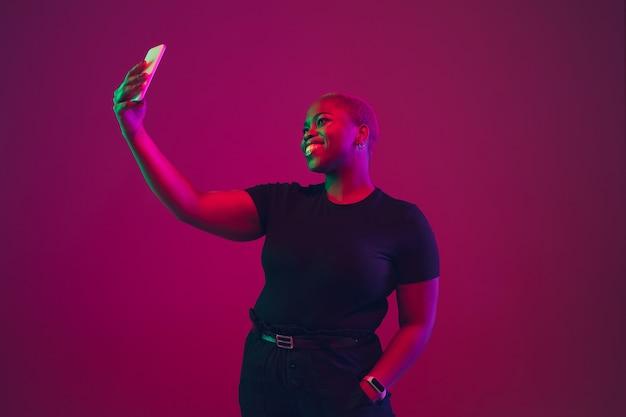 Retrato de mujer joven afroamericana en rosa púrpura en neón