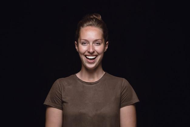 Retrato de mujer joven aislada sobre fondo negro de estudio de cerca. photoshot de emociones reales de modelo femenino. sonriendo, sintiéndose locamente feliz, riendo. expresión facial, concepto de emociones humanas.