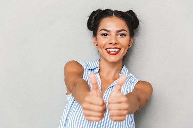 Retrato de una mujer joven alegre aislada, mostrando los pulgares para arriba