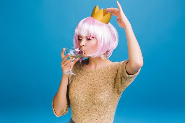 Retrato de mujer joven alegre con corte de pelo rosa bebiendo champán con cerrado. maquillaje brillante con oropel rosa, feliz celebración, fiesta de año nuevo, cumpleaños.