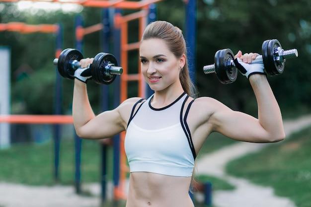 Retrato de la mujer joven alegre en el desgaste de la aptitud que ejercita con pesas de gimnasia negras en parque