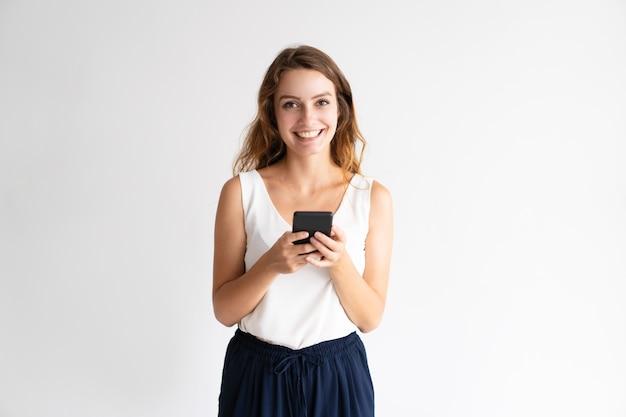 Retrato de la mujer joven alegre que se coloca y que usa el teléfono móvil.