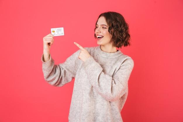 Retrato de una mujer joven alegre que se encuentran aisladas sobre rosa, presentando tarjeta de crédito de plástico