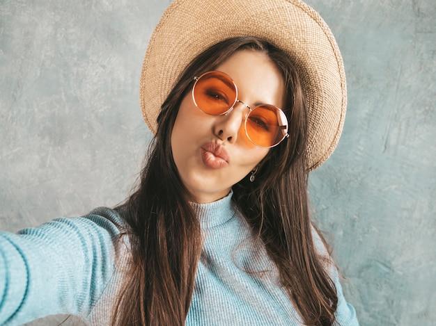 Retrato de mujer joven alegre tomando foto selfie y vistiendo ropa moderna y sombrero.