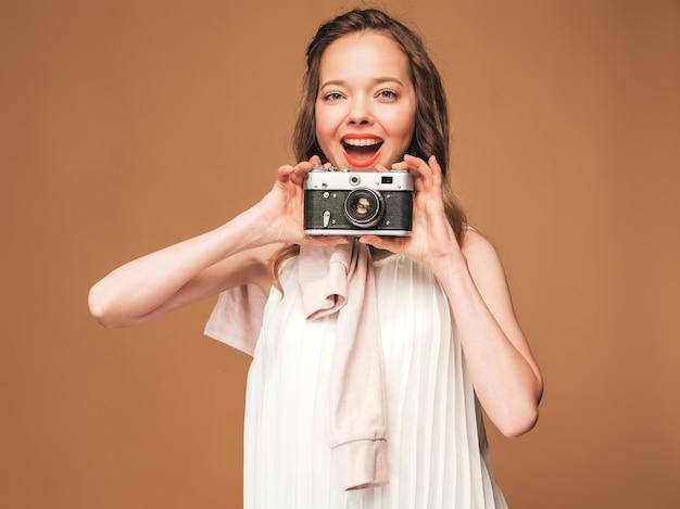 Retrato de mujer joven alegre tomando fotos con inspiración y vestido blanco. chica sosteniendo la cámara retro. modelo posando