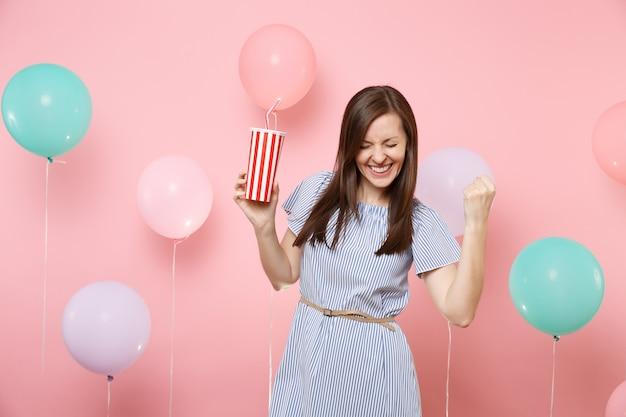 Retrato de mujer joven alegre en vestido azul con los ojos cerrados haciendo gesto de ganador diciendo sí, sosteniendo un vaso de plástico de cola o soda sobre fondo rosa con globos de colores. fiesta de cumpleaños.