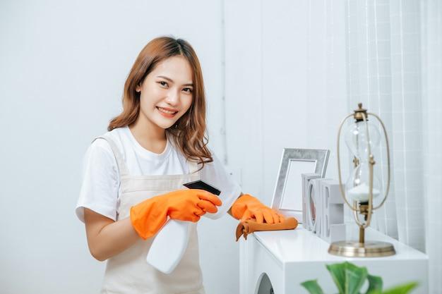 Retrato mujer joven ama de llaves con delantal y guantes de goma, use una solución de limpieza en una botella de spray sobre muebles blancos y use un paño para limpiarlo