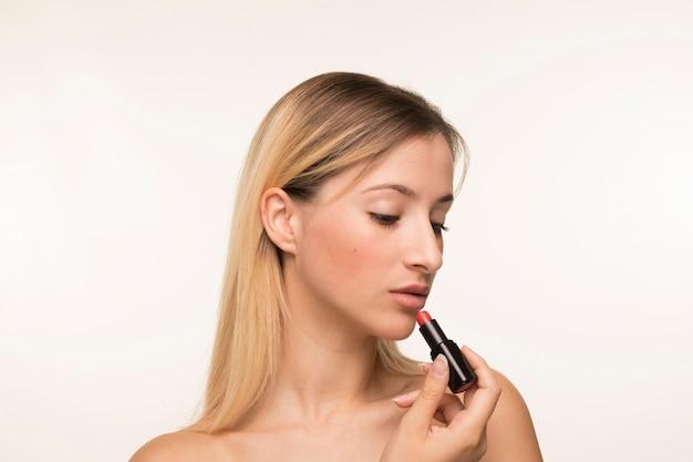 Retrato de mujer joven aplicar lápiz labial